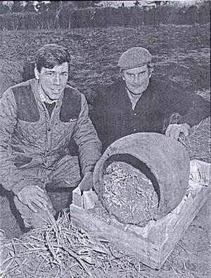 Photograph of farmer Andrew Carver, left, and his foreman, John Lester, with a Bronze Age burial urn from Alpington.