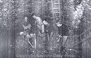 Photograph of volunteers at work in the bottom of the ice house in the grounds of Felbrigg Hall.