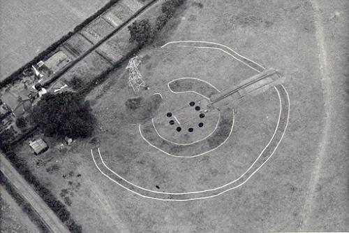 Aerial photograph of Arminghall Henge taken during excavation in 1935. White lines show the outlines of the ditches and the black dots mark the position of the central timbers.