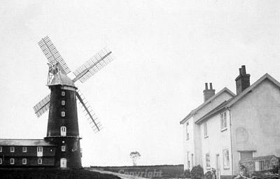 Photograph of Caston Mill, a six storey brick tower mill, built in 1864 to replace a post mill. The mill has a boat-shaped cap. The photograph is from www.norfolkmills.co.uk