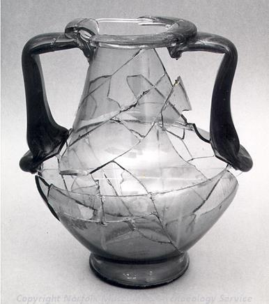 Photograph of a Roman glass vessel that was used to contain an infant cremation found in Geldestone. Accompanying the cremated infant bones were a bronze casket mount and a Roman coin. The burial was discovered in 1849.