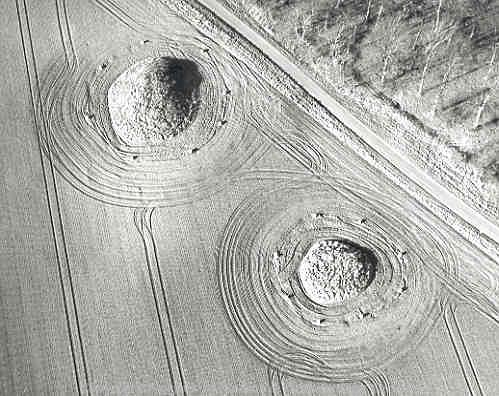 Aerial photograph of Bronze Age round barrows at Harpley. The concrete posts around the barrows protect them from ploughing.