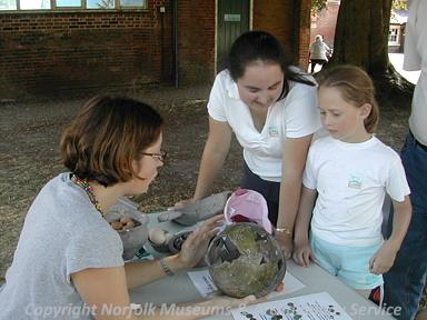 Megan Dennis (NLA) showing visitors a medieval Grimston green glazed pot during Archaeology Week at Gressenhall Farm and Workhouse in Summer 2006