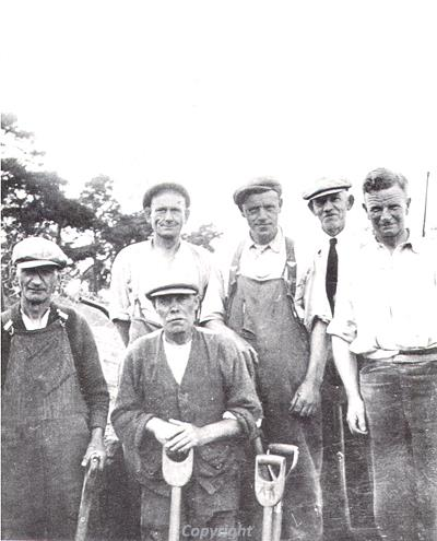 Photograph of Group Captain Knocker (on far right) with a group of excavators.