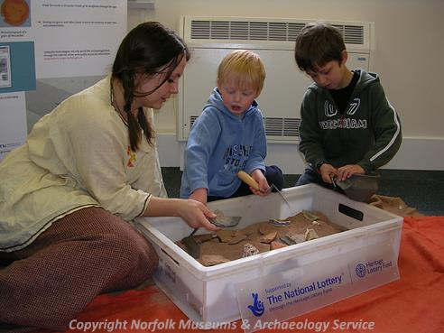 Photograph of Norfolk Heritage Explorer volunteer Charis Woodbridge and children exploring the archaeology sand tray at Watton Library Heritage Family Fun Day.