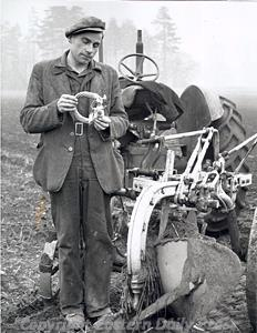 Photograph of the finder of the first torcs to be discovered at Snettisham in the 1940s with a group of torcs.