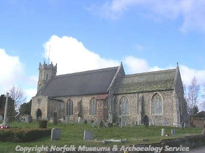 St Edmund's Church in Acle, showing the 12th century round tower and the 15th century two-storey porch.