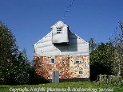Shows the weatherboarded and brick mill and sack hoist.