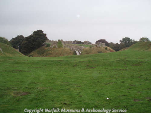 View of the castle ruins from the far end of the bailey, with earthworks of the bailey in the foreground.