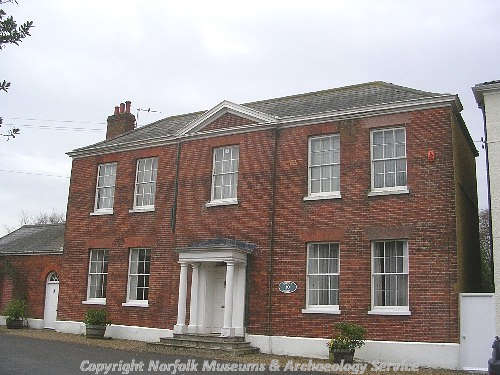 The mid 18th century facade of Quorn House, Hingham, showing the slightly advanced central bay with a pediment and a porch.