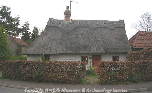Hill Cottage from the road, showing the single storey structure with a thatched roof.