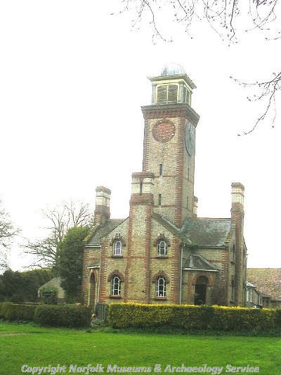 The 19th century clock tower at Little Ellingham Hall showing the cupola and the surrounding cottages.