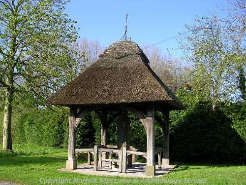 The 19th century pump standing under a thatched roof.
