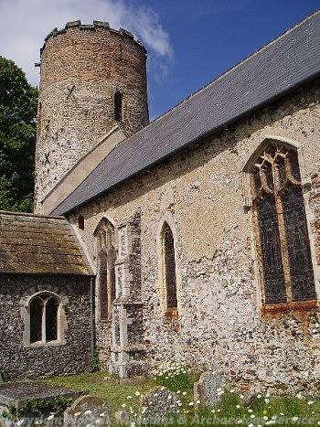 View of SS Peter and Paul's Church in Burgh Castle showing the Late Saxon round tower, the nave and the late 19th century south porch.