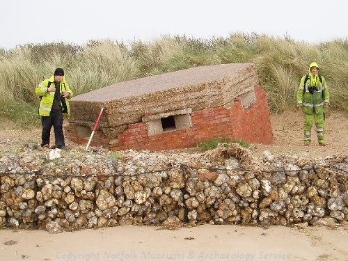 A World War Two pillbox in front of sand dunes.