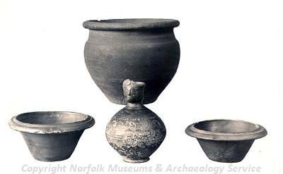 Photograph of four Roman vessels, including one decorated with a human face.